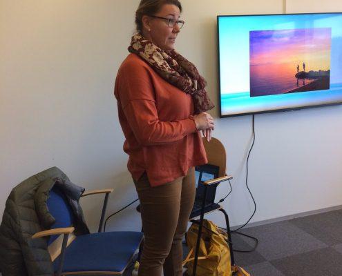 Kuvassa on Heli Nissinen kertomassa tietoisesta läsnäolosta. Helillä on punartava paita, ruskeat housut, vaaleanruskeat kengät ja ruskean kirjava huivi. Seinällä on Tukipilarin infotelevisio, josta näkyy punertava auringonlasku ja laituri.