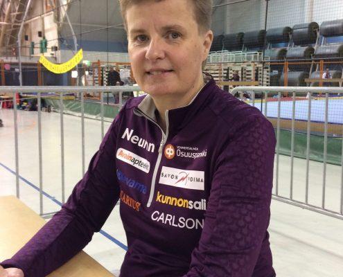 Urheilija Marjaana Heikkinen istuu pyörätuolissa pöydän ääressä FYM17 -tapahtumassa 16.9.2017. Hänellä on yllään violetti urheilupaita, jossa on logoja. Heikkisellä on vaaleat lyhyet hiukset.