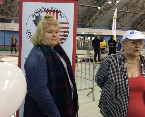 Pohjois-Savon Lihastautiyhdistyksen pisteellä jaettavana oli Porras -lehtiä. Kuvassa vaaleahiuksiset naisesittelijät. Taustalla on yhdistyksen roll up.