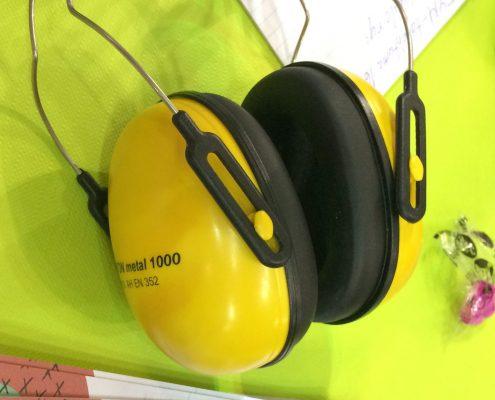 Kuopion kuulo ry jakoi FYM17 -tapahtumassa pinkkejä korvatulppia. Kuvassa vihreänkeltaisella pöytäliinalla lepäävät keltaiset rakennustyökuulokkeet ja vieressä ovat pinkit korvatulpat pienessä pussissa.
