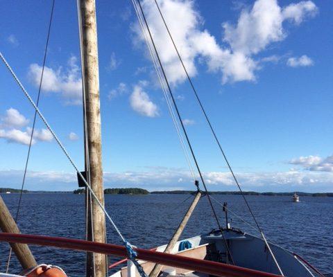 Kuvassa laivan masto etualalla. Taka-alla vettä ja sinistä taivasta.