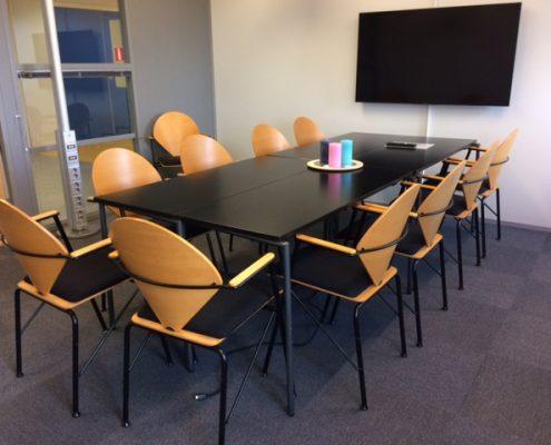 Kuvassa Tukipilarin kokoustila. Kokoustilassa on läpinäkyvät ikkunat käytävälle päin. Kokoustilassa on iso pöytä, jonka voi jakaa 4 osaan ja pöydän ympärillä 10 tuolia. Seinällä on iso näyttö.
