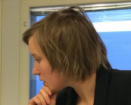 Palvelumuotoilija Kirsi Miettinen auttaa yhdistyksiä kehittämistyössä Tukipilarin kehitysverstaassa. Kuvassa miettinen seisoo ikkunan edessä, miettii ja pitää leuastaan kädellä kiinni. Hänellä on rikottu polkkatukka, musta jakku ja violetti pusero.