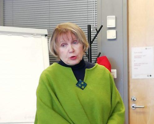 Lea Lihavainen Opintokeskus Siviksestä vei meidät kokouskäytäntöjen saloihin. Kuvassa nainen, jolla on vaaleat polkkatukkaiset hiukset, vaaleanvihreä poncho ja sen alla musta paita. Nainen seisoo Tukipilarin kokoustilassa.