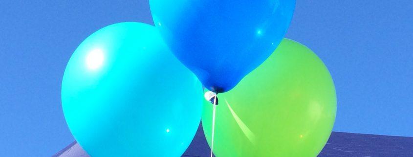 Turkoosi, sininen ja vihreä ilmapallo Tukipilarin teltalla Olonkorjuutorilla.