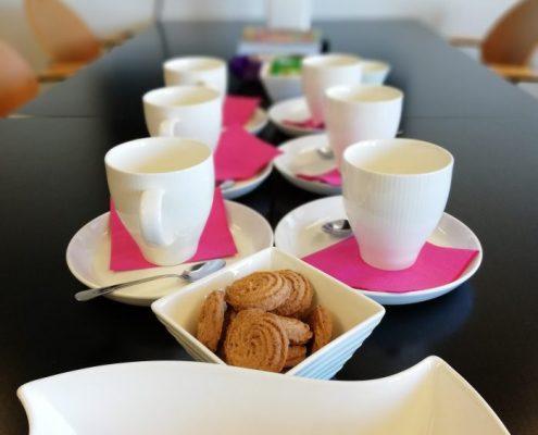 Avoimien ovien päivässä 18.9. kahvitarjoilu odotti vierailijoita. Kuvassa on valkoisia kahvimukeja valkoisilla lautasilla pinkkien lautasliinojen kanssa. Kuvan etualalla on keksejä neliskulmaisissa astioissa. Kuvan taustaosa on sumea.