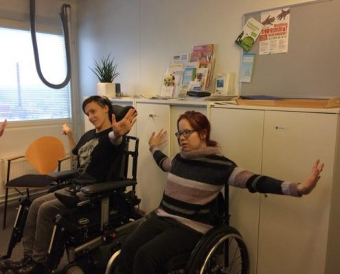 Helmikuun tuolijoogassa kädet saivat liikettä. Kuvassa kaksi naista harrastaa tuolijoogaa. He istuvat ja levittävät kätensä sivuilleen painaen kuvitteellista seinää.