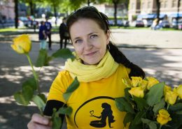 Nainen keltaisessa paidassa jakamassa keltaisia ruusuja