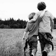 Kaksi poikaa kävelee poispäin vierekkäin