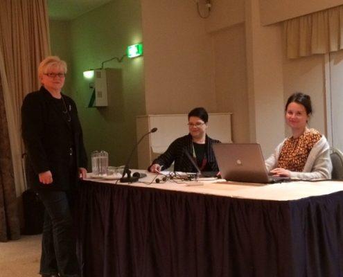 Tuula Väätäinen, Sanna Vesterinen ja Pinja Nieminen tekevät viime hetken valmisteluja Valikko-seminaaria varten marraskuussa 2017. Kaksi heistä istuu pöydän ympärillä ja yksi heistä seisoo.